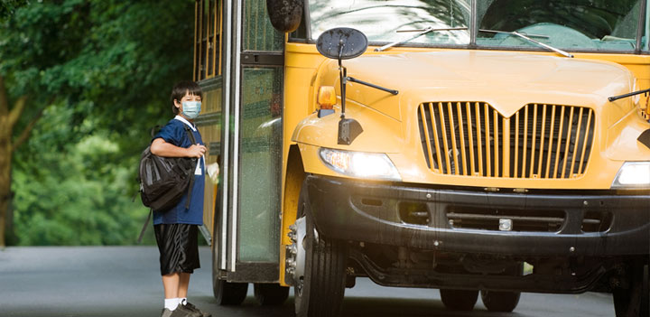 boy in mask getting on bus
