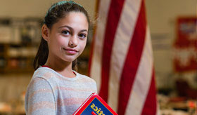 A girl in front of a flag